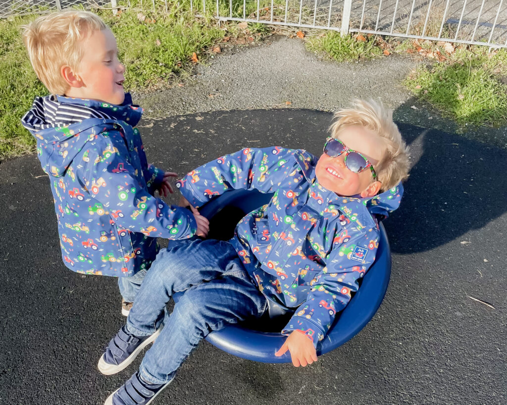 Three year old twin boys wearing purple coats with tractors on and jeans, play in a swivel seat at a play park