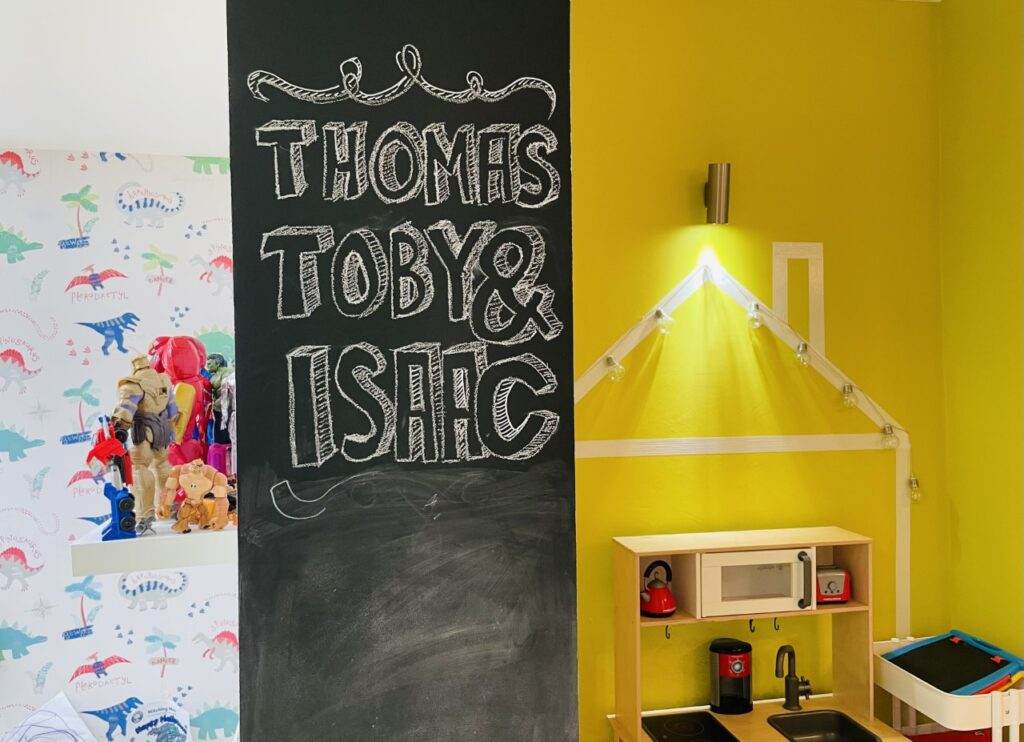 A strip of blackboard wall in a playroom with the names Thomas, Toby and Isaac written on it in white chalk