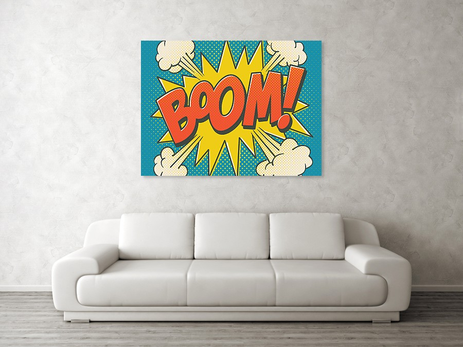 A white sofa next to a grey wall. Above the sofa is a green,yellow and red poster print of the word Boom