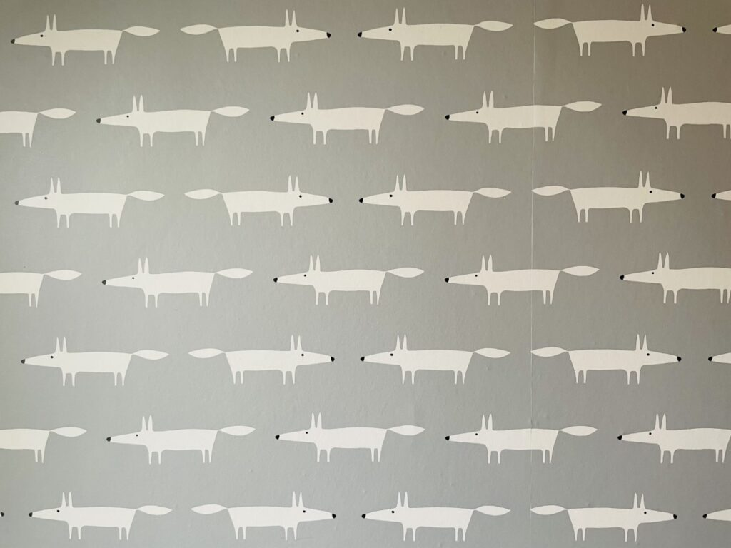 Grey wallpaper with white foxes on it