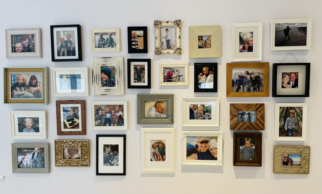 A piece of wall art consisting of a picture gallery of family photos on a kitchen wall