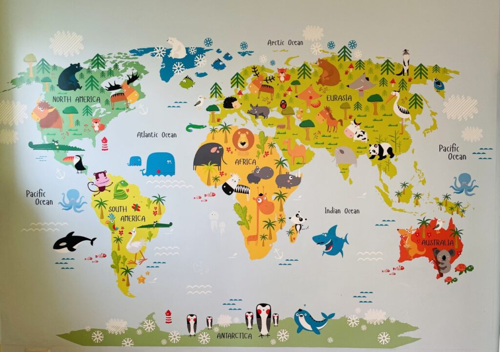 A piece of wall art cartoon map of the world with animals on the wall of a playroom