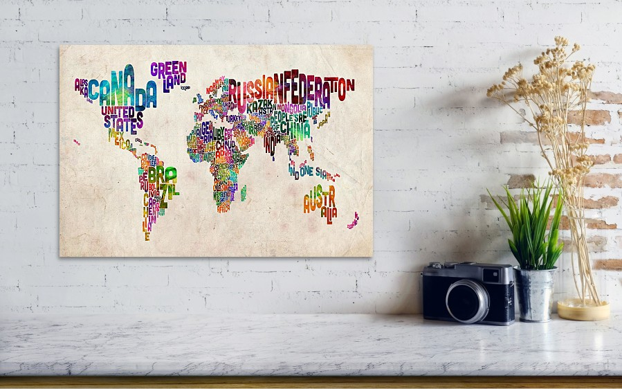 A grey wall and shelf with camera on it, with a map of the world picture on the wall. Countries on the map are made out of different words of countries