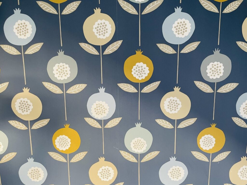 Blue wallpaper with mustard, beige and light blue flowers on it