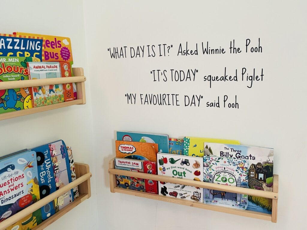 A wall with wooden bookshelves full of children's books plus a quote from Winnie the Pooh in black stickers on the wall