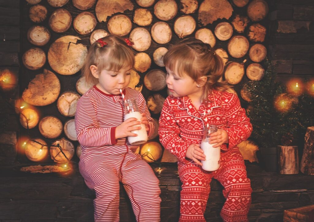 Two toddler girls wearing red pyjamas in front of a log pile as an idea for what to put in Christmas Eve Boxes