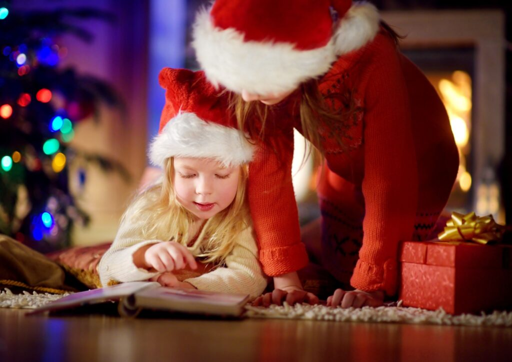 Little girl and mum in santa hats on the floor reading a book with a Christmas tree in the back ground