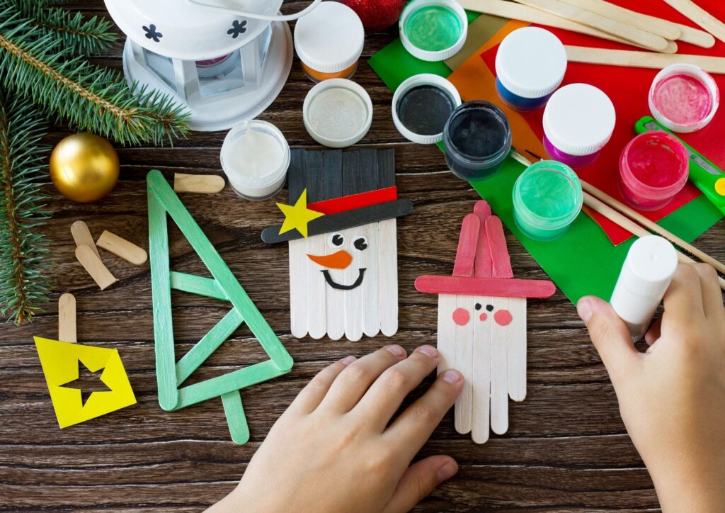 Table of Christmas crafts, paints and snowmen, santa and tree made out of lolly sticks. An idea for Christmas Eve Boxes.