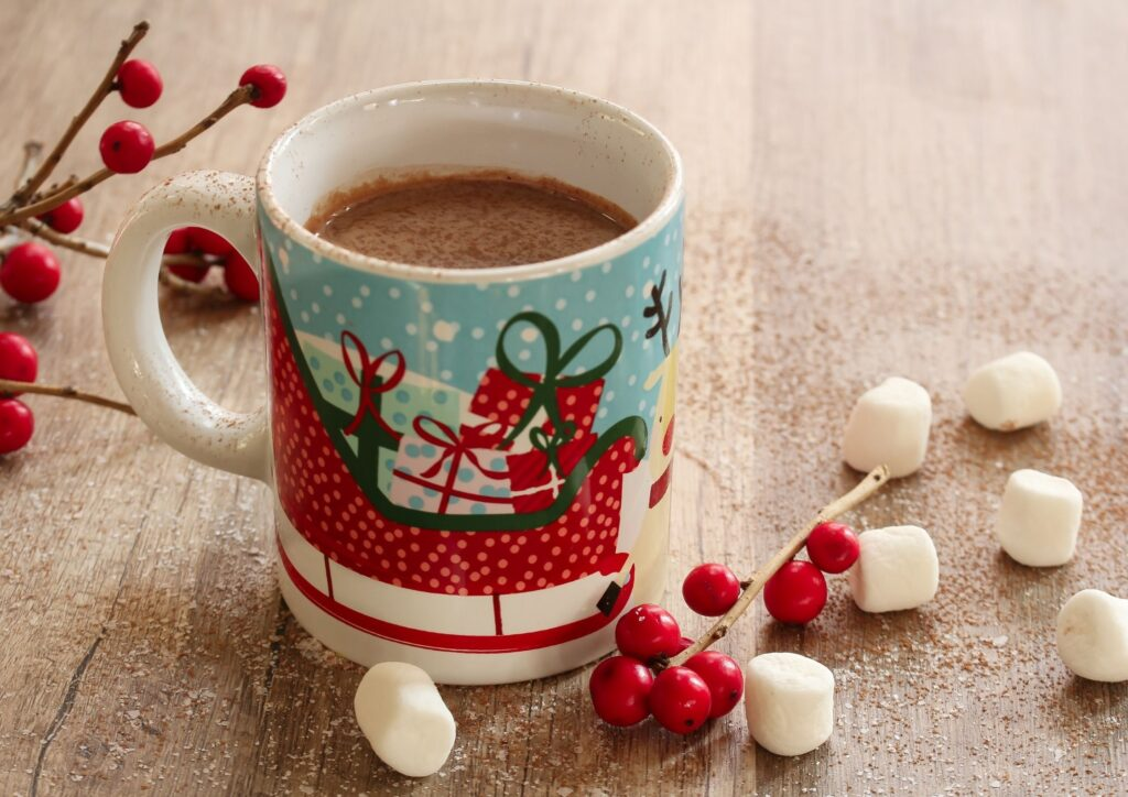 Christmas mug with hot chocolate and marshmallows next to it. An idea for Christmas Eve Boxes.
