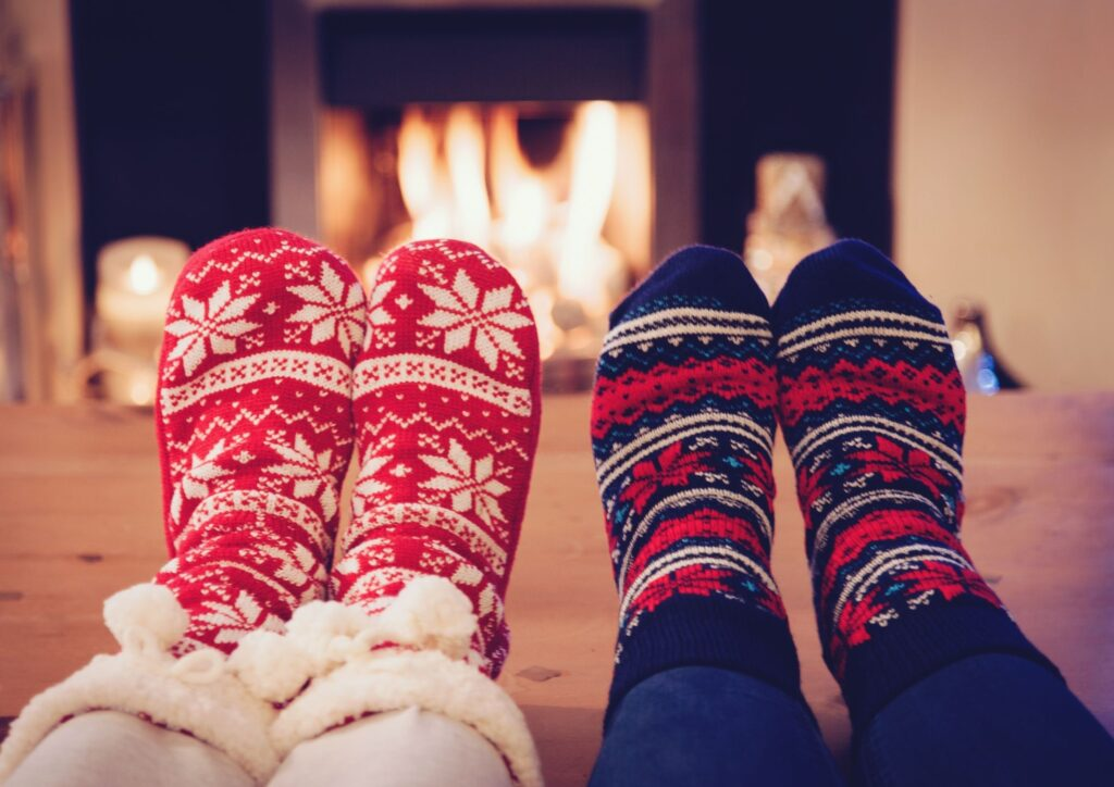 Two pairs of feet in front of a roaring fire wearing festive socks