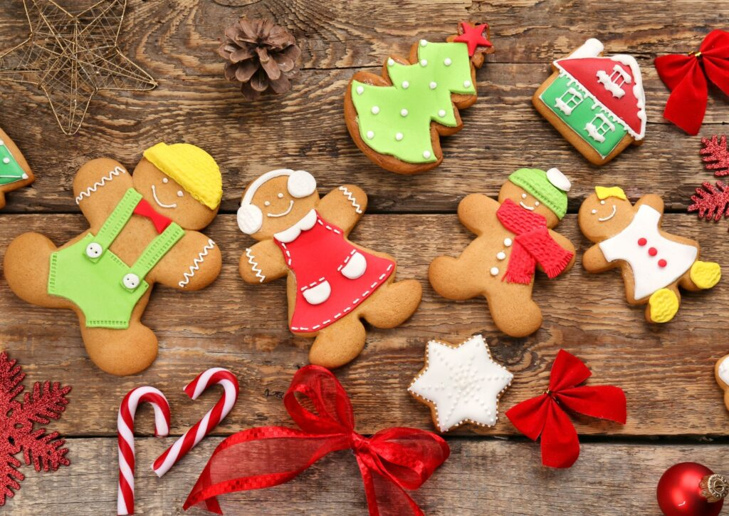 Gingerbread men biscuits on a wooden table with christmas decorations. An idea for Christmas Eve Boxes.
