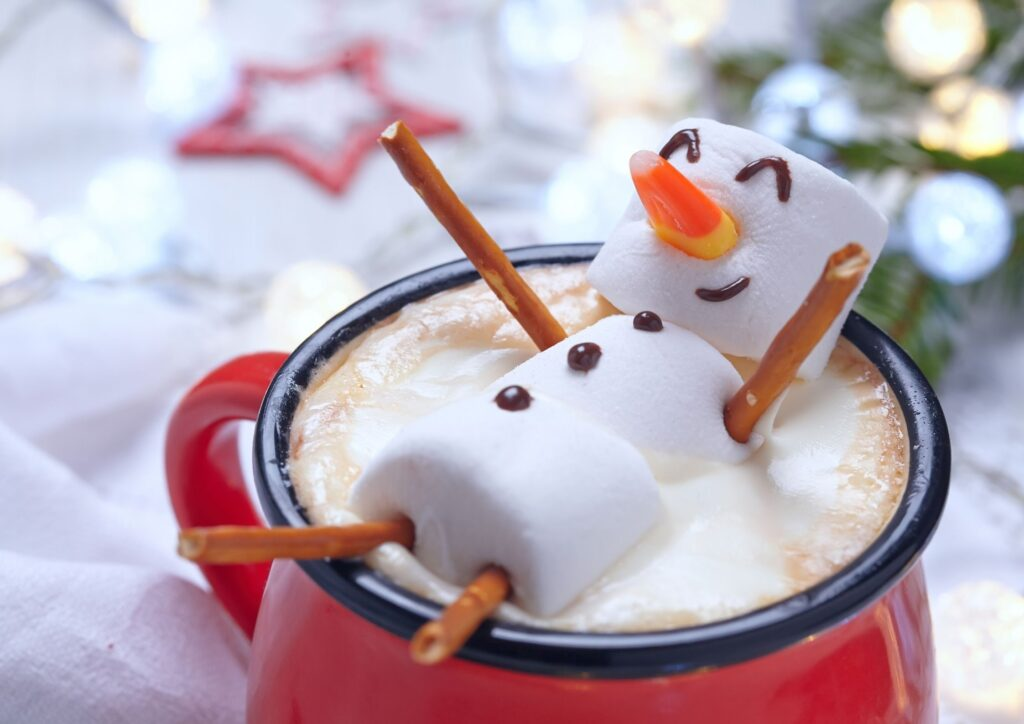 Marshmallows in the shape of a snowman resting on the top of a hot chocolate