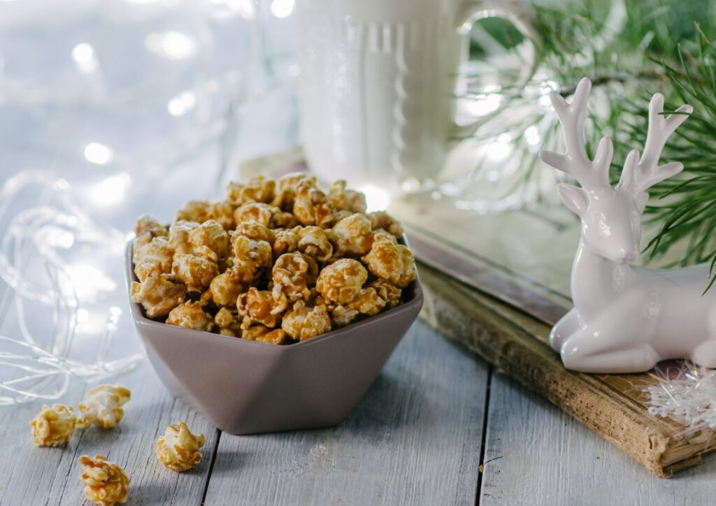 Popcorn in a white bowl next to fairy lights