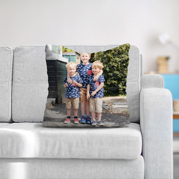 A cushion with a print of three boys on it