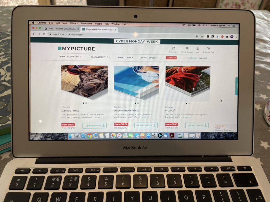A laptop screen on a table showing a website where you can print out photos