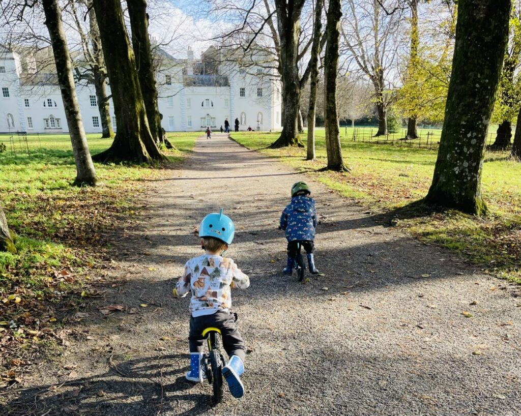 Two little boys on balance bikes riding along a tree lined avenue towards Saltram House as a Plymouth place to visit in Tier 3