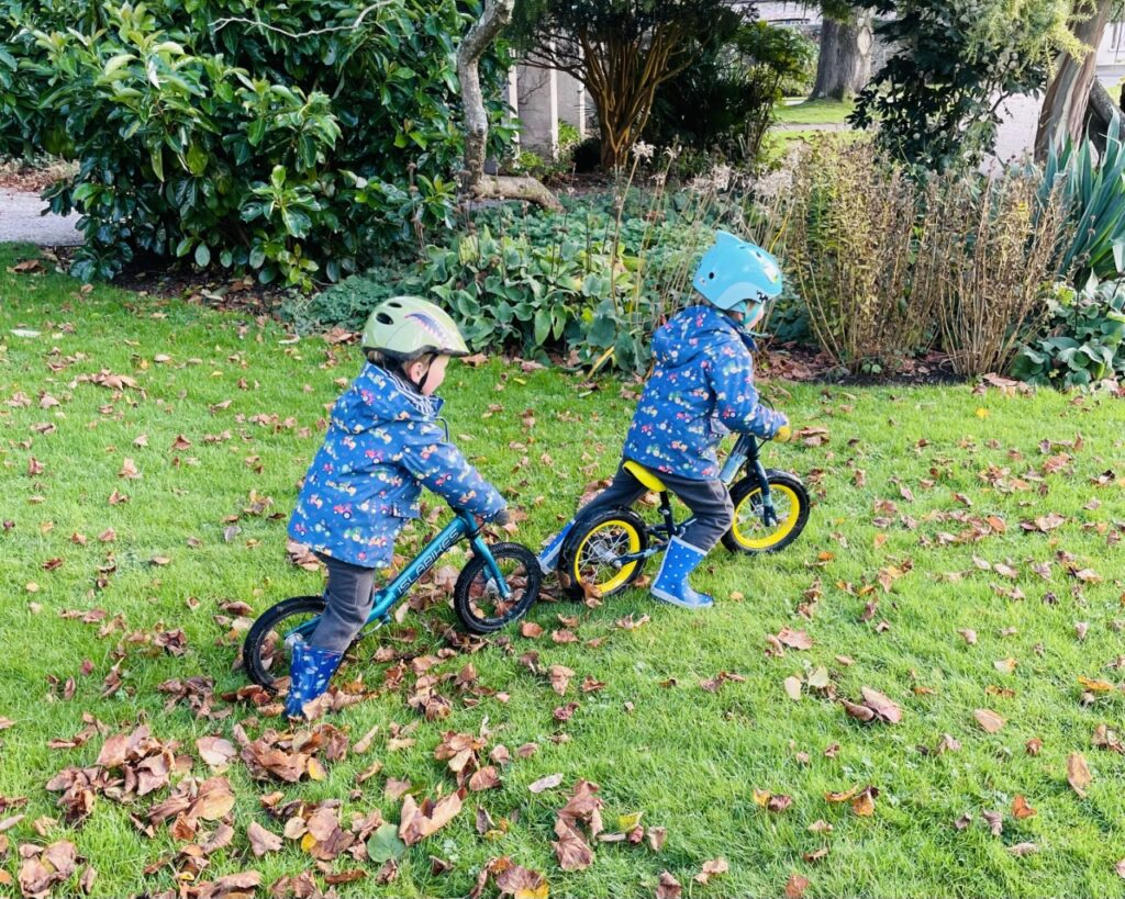 Twin boys riding balance bikes on the grass