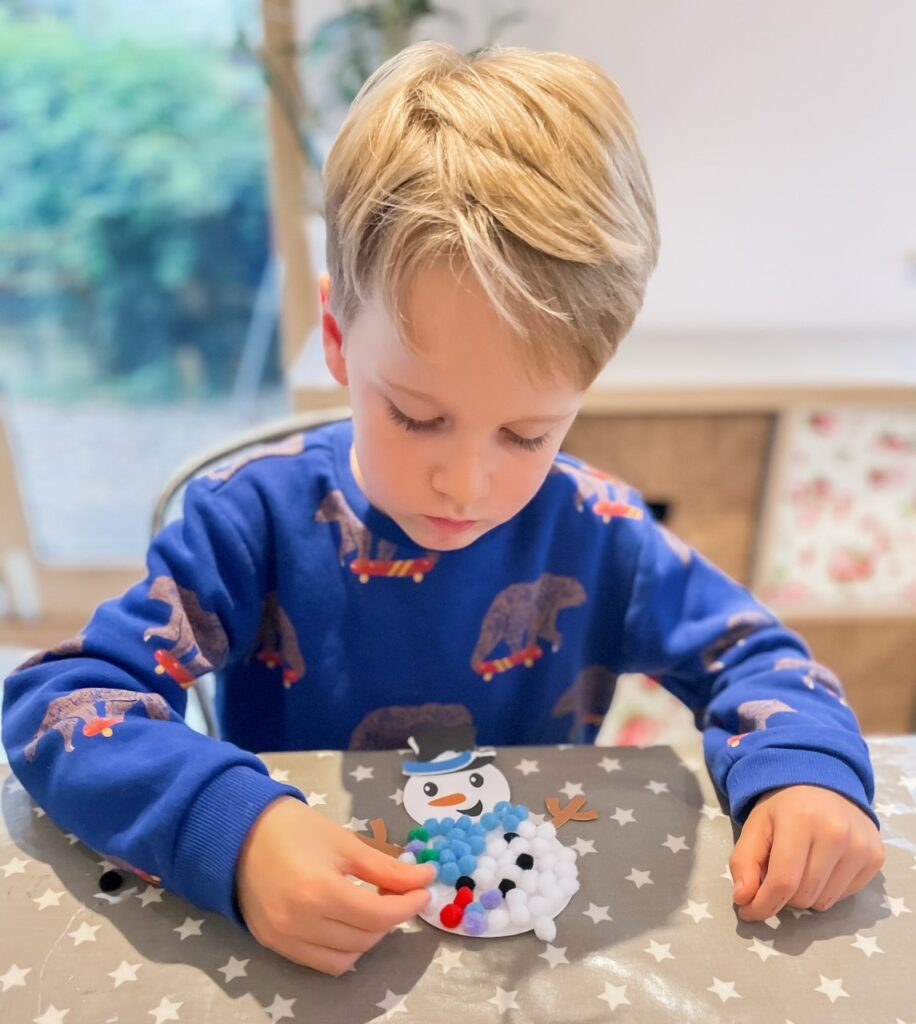 Five year old boy sat at a table doing christmas craft sticking pom poms onto a snowman