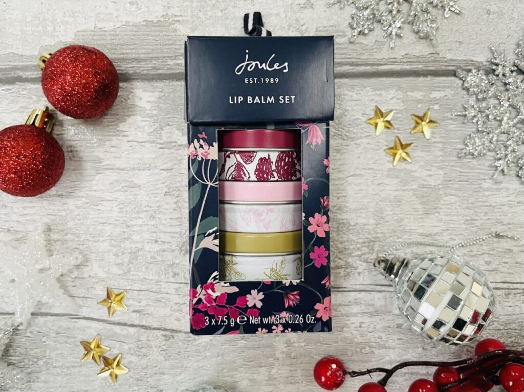 Joules lip balm set surrounded by christmas decorations