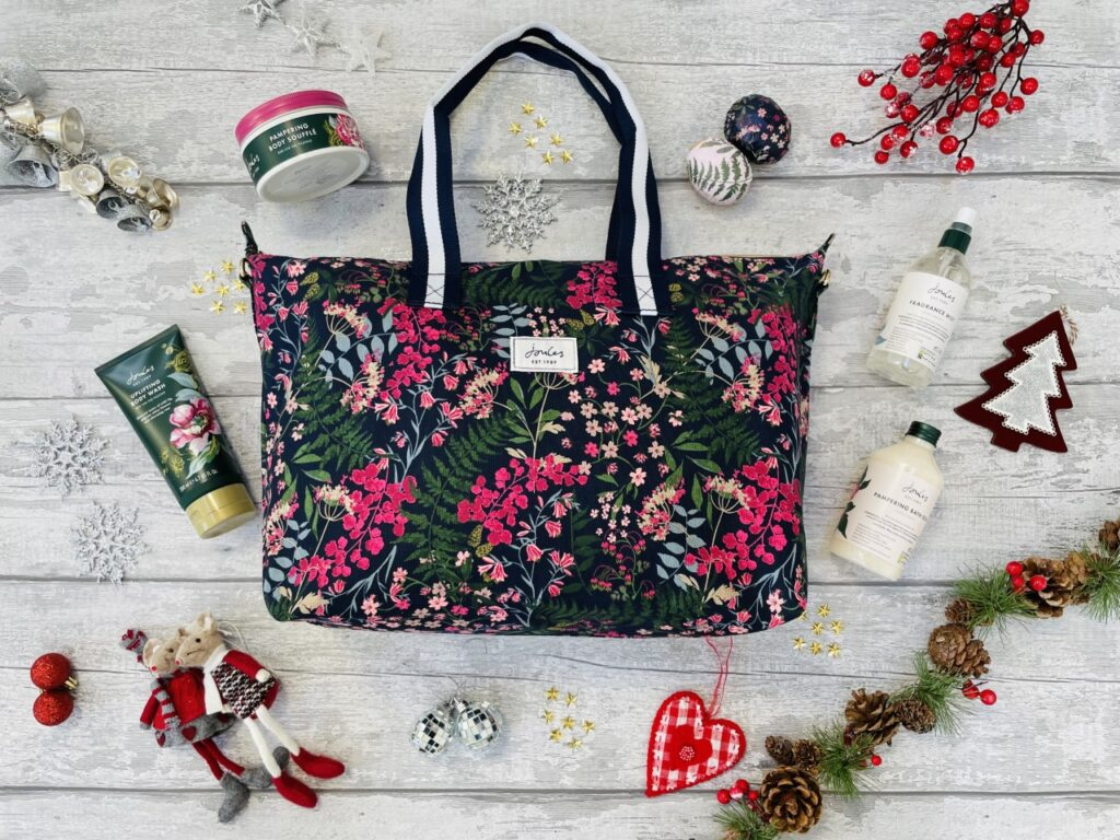 A pink and navy flowery joules bag with various bottles of pampering items on a grey background surrounded by christmas decorations