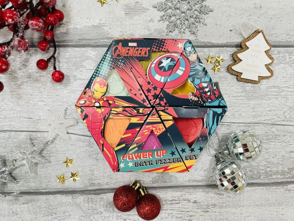 Avengers bath fizzers set surrounded by Christmas decorations on a grey background