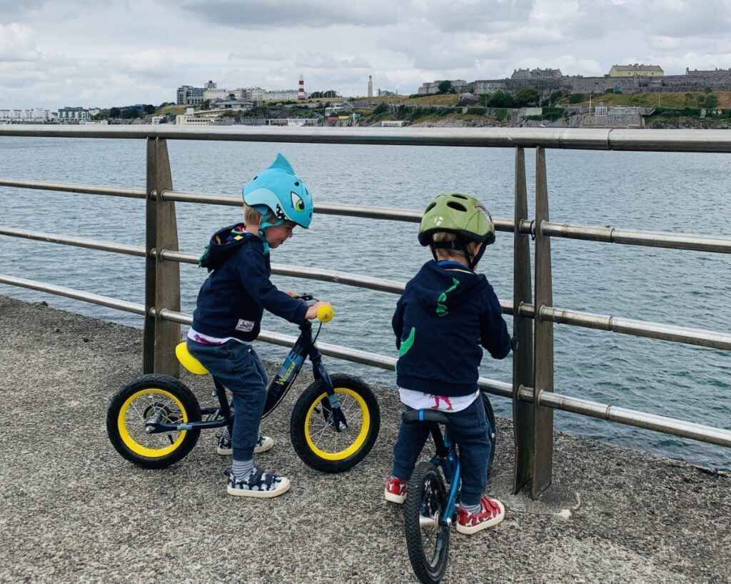 Two little boys on balance bike near a fence on a pier into Plymouth Sound