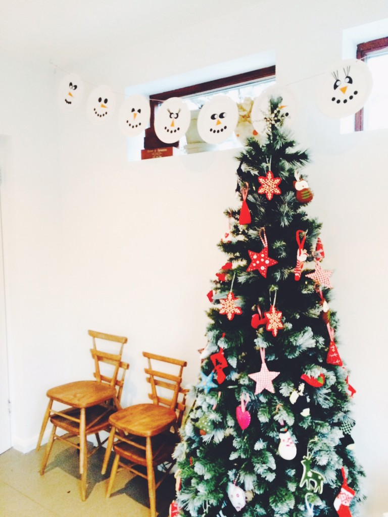 Christmas craft snowmen paper plate bunting hung on a wall above a Christmas tree