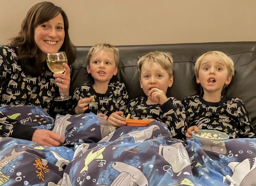 Mum and three boys in matching pyjamas keeping warm under a duvet on the sofa