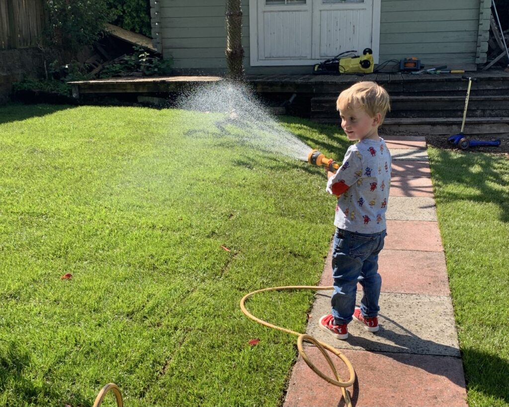 Toddler is encouraged to be playing outside by watering the grass