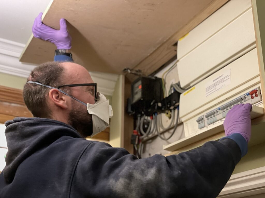 Electrician wearing a face mask and gloves checks a fuse box for a piece about tradespeople in your home during Covid