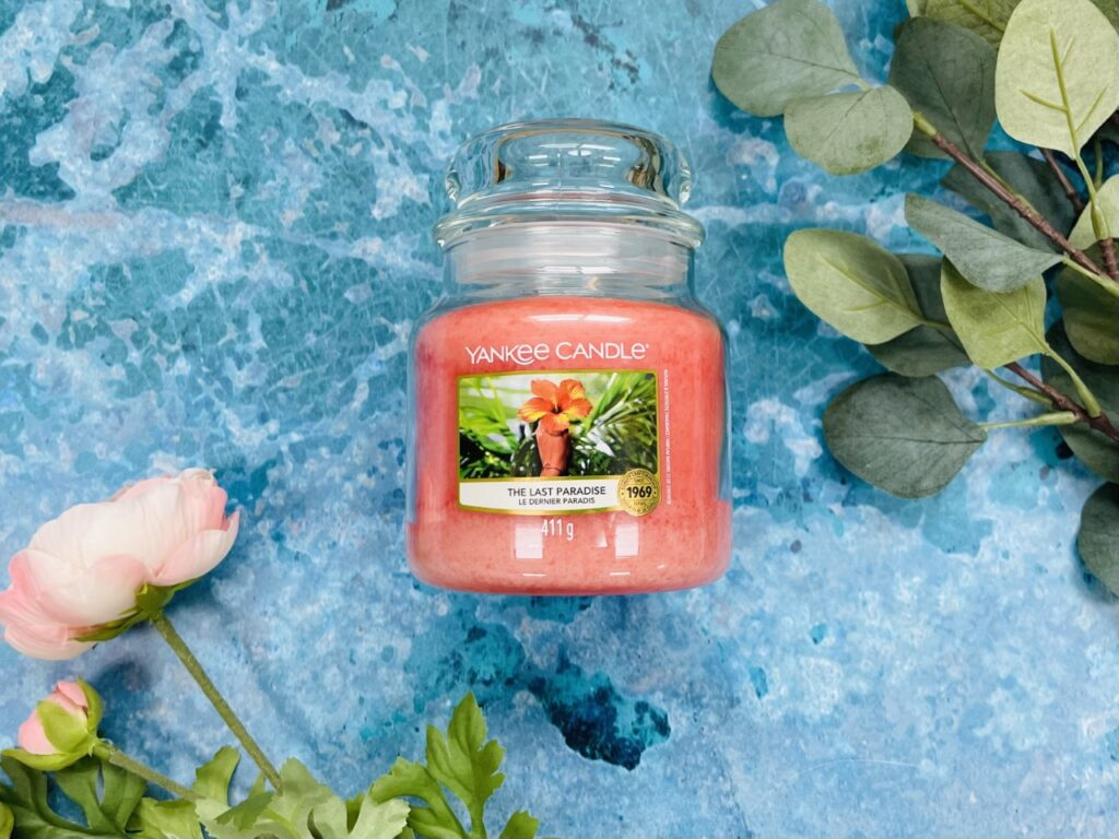Pink yankee candle in a glass jar on a blue background with flowers and leaves