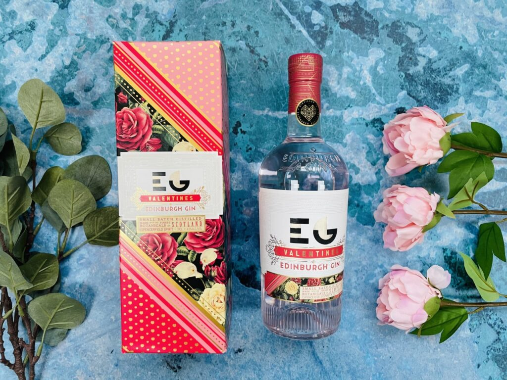 Bottle of Edinburgh gin with the box on a blue background and flowers for Valentine's Day in lockdown
