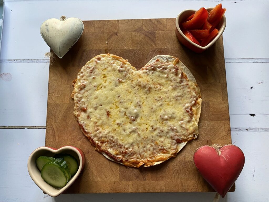 Heart shaped pizza on a wooden board as an idea of how to celebrate Valentine's Day in lockdown