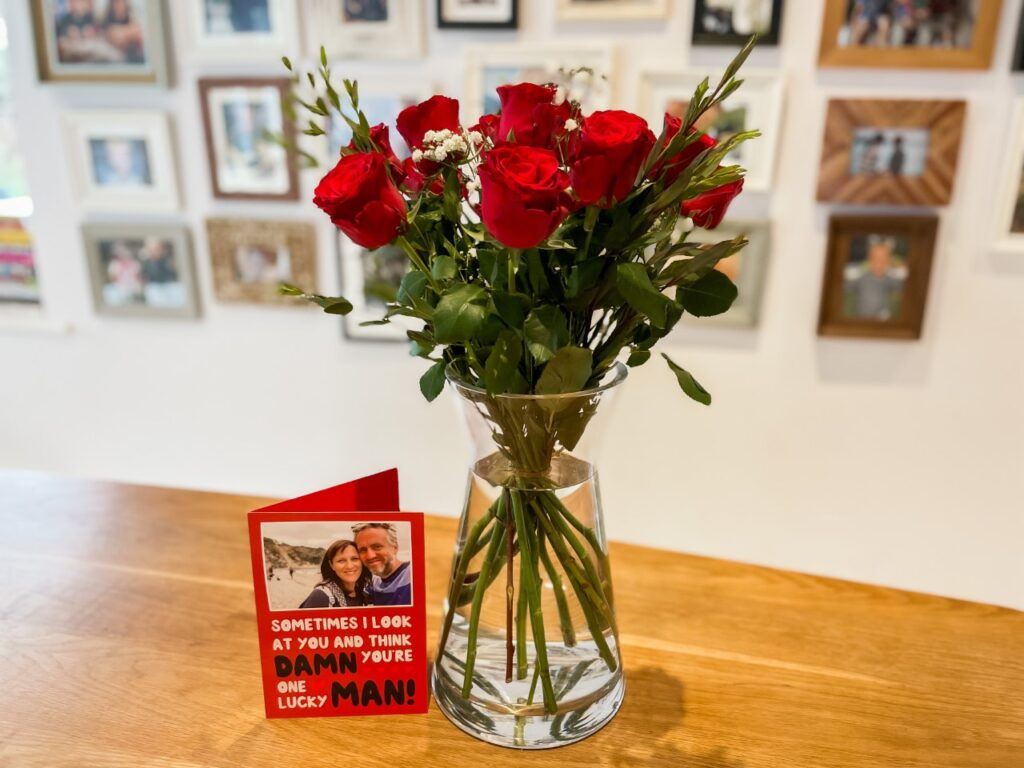 Roses and a card with photo frames in the background as an idea of how to celebrate Valentine's Day in lockdown