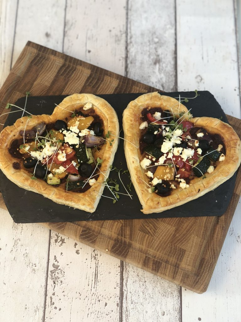 Heart shaped veggie tarts on a black slate plate and wooden board