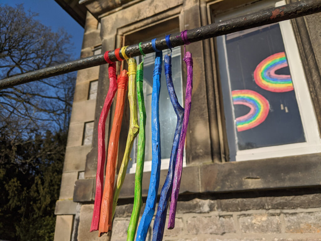Sticks painted in rainbow colours hanging on a pole, as an activity to do in a half term in lockdown