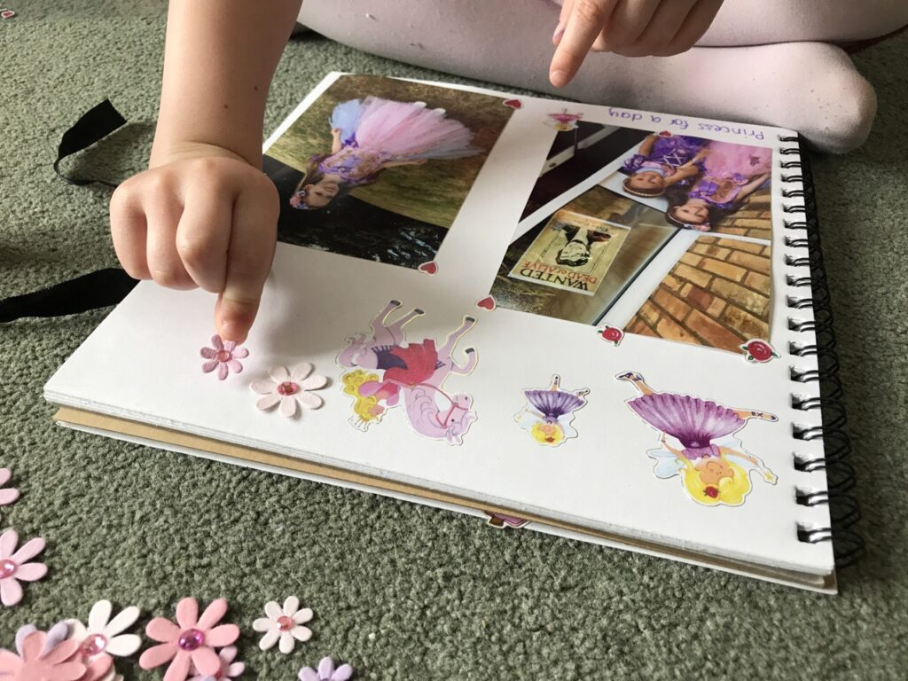 A girl's hand sticking stickers into a scrapbook around photos