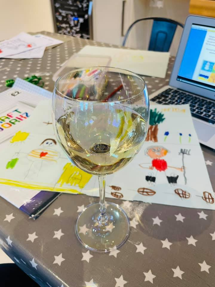 A glass of white wine in front of a laptop and children's colourings