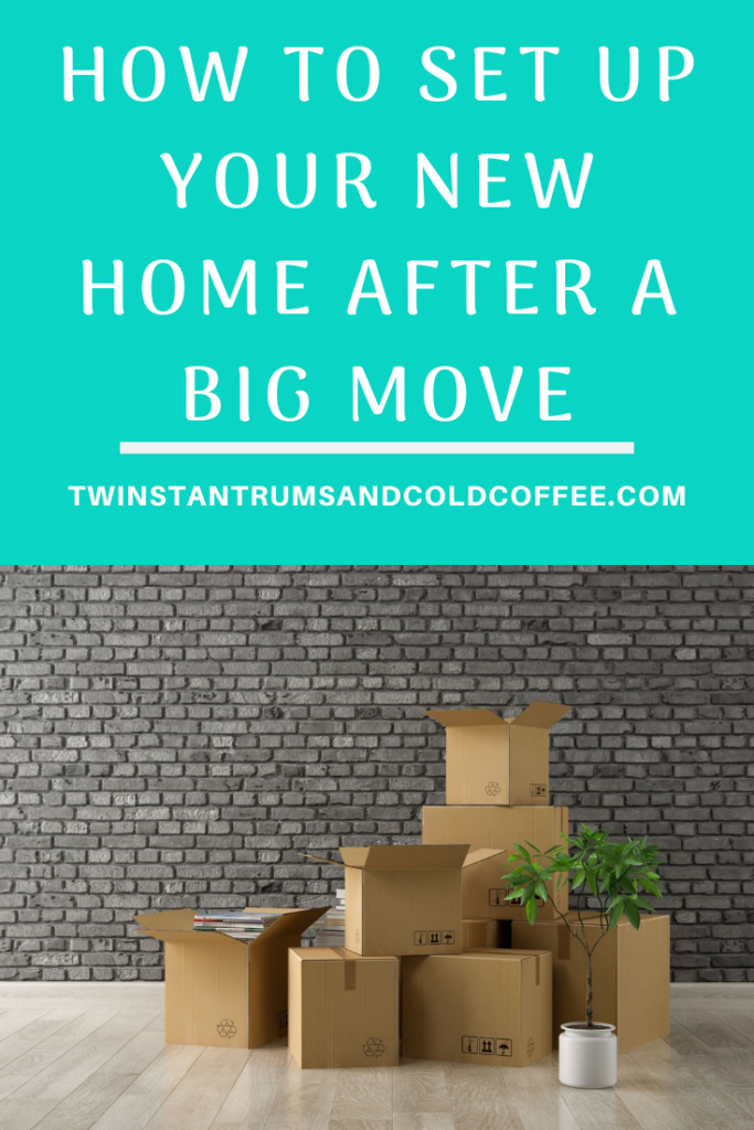 How to set up your new home after a big move with a pile of boxes against a brick wall in an empty room