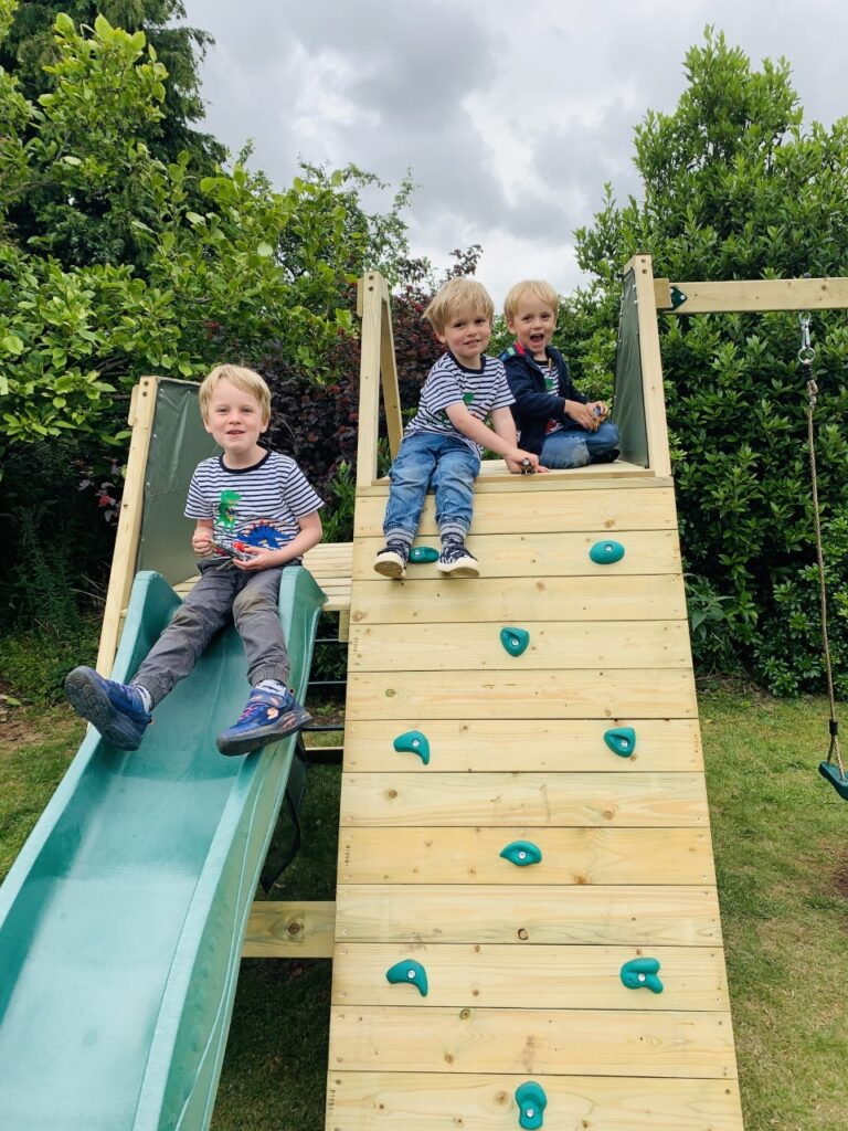 Three brothers sitting on the top of a wooden climbing wall and slide in their back garden