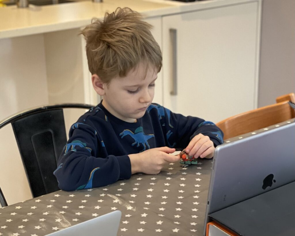 Five year old boy sitting at a table playing with a lego mini figure during a homeschooling video