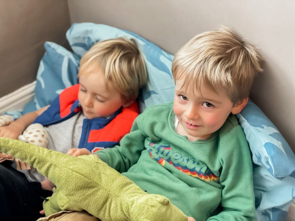 Three year old twin boys under a duvet in a den