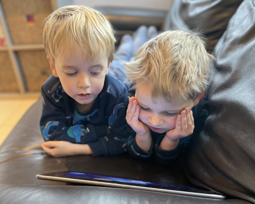 Three year old twin boys lying on a settee and watching the ipad
