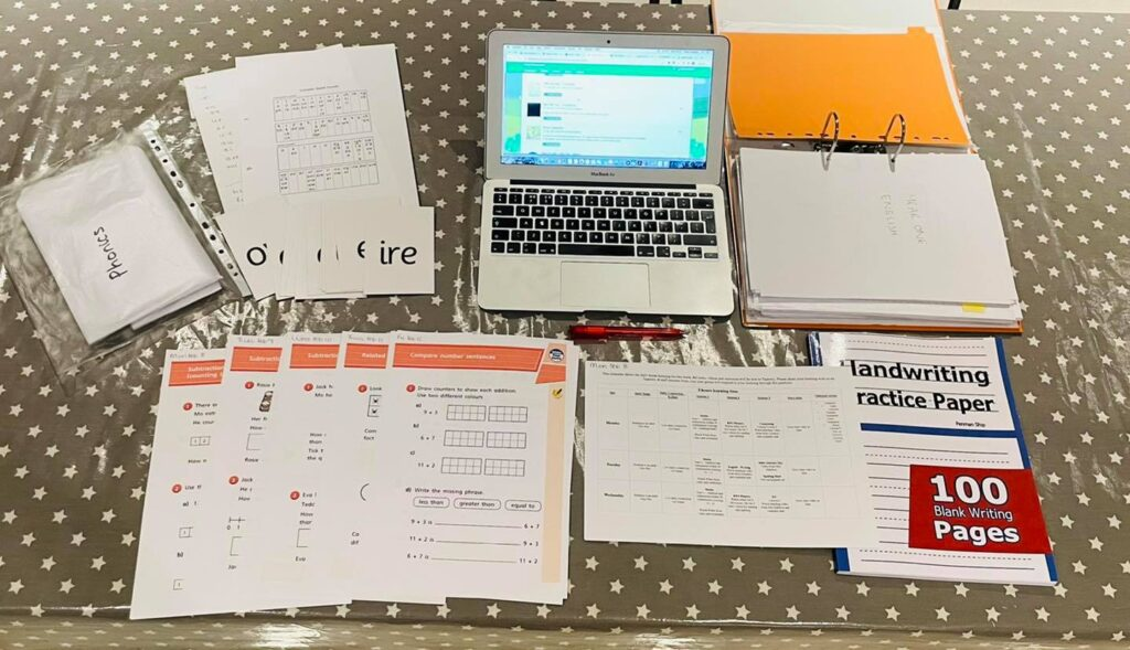 preparation for a week of homeschooling including a laptop, worksheets and print outs on a kitchen table