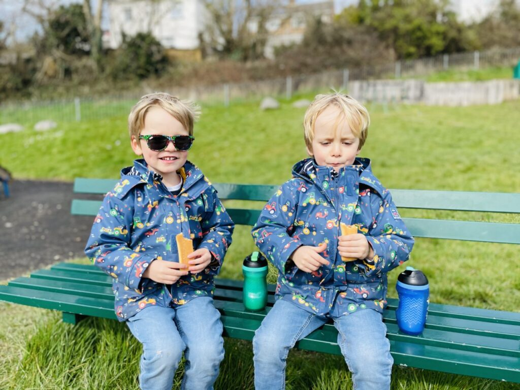 Three year old twin boys wearing purple tractor coats sitting on a bench in a park drinking and having a snack