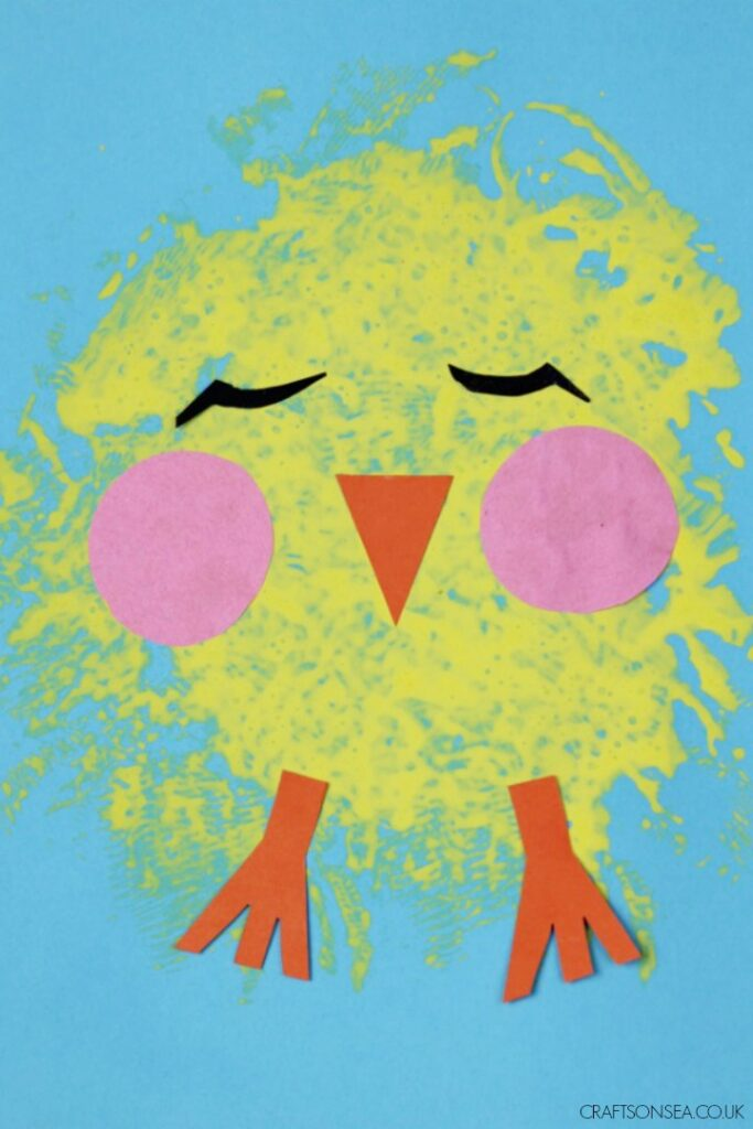 A yellow easter chick made out of sponge painting on a blue background