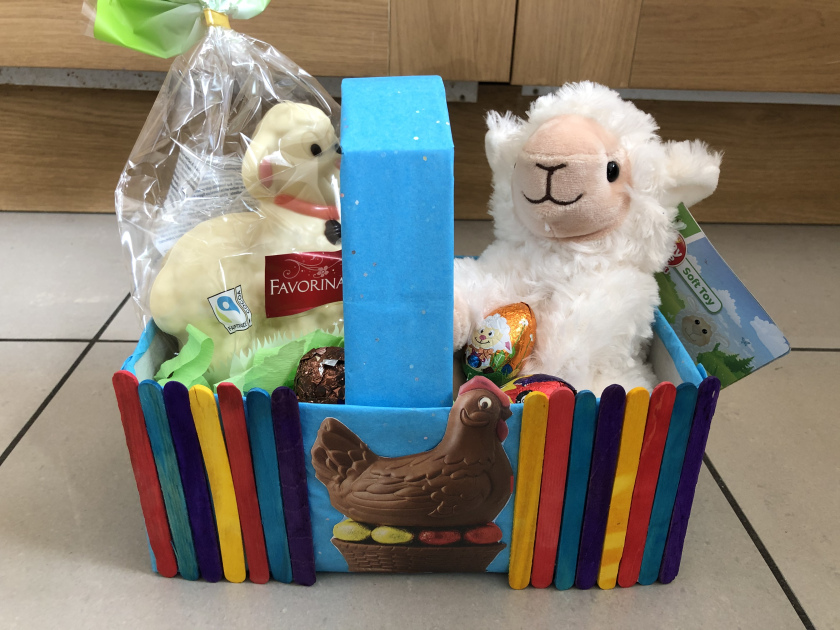 A cuddly sheep and some chocolate inside a homemade easter basket