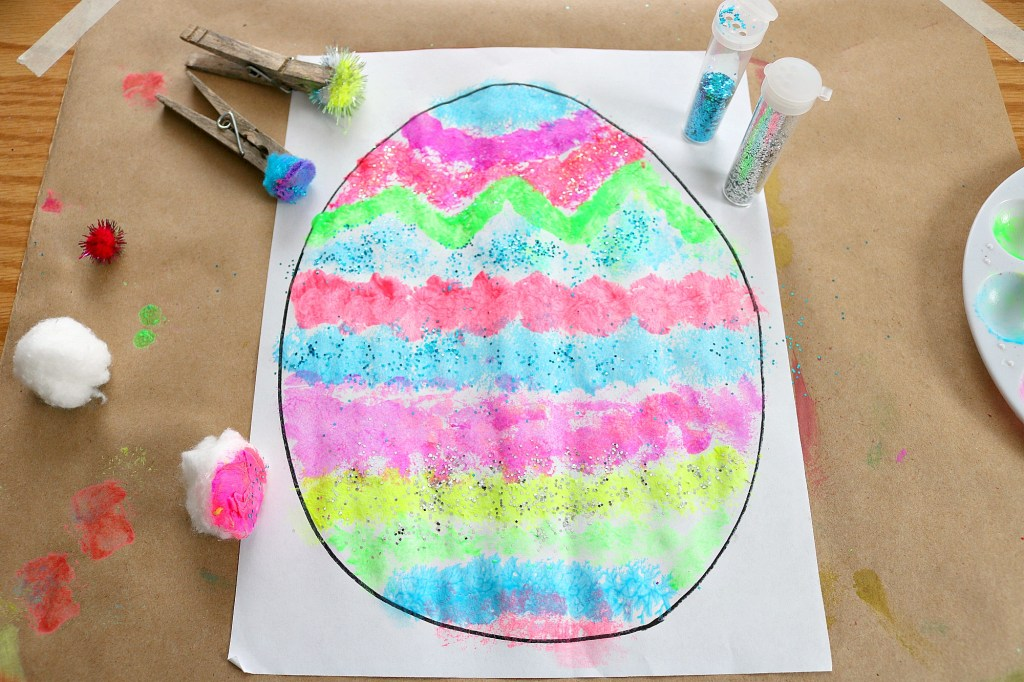 Easter craft idea of using pom poms to paint an outline of an easter egg