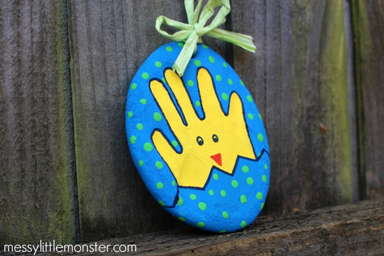 A salt dough decoration with a hand print Easter chick painted yellow on it and a blue spotty background
