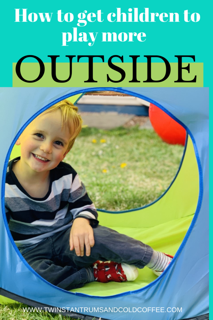 Little blonde boy inside a pop up tent in the garden as a way of getting children outside more